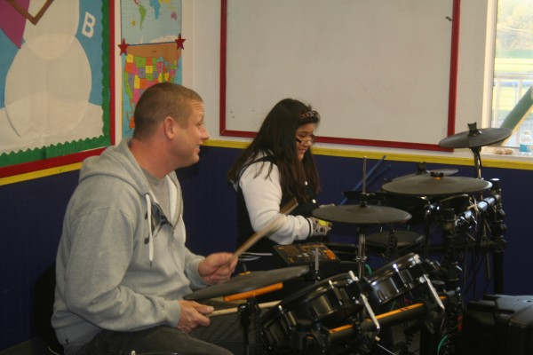 Drummer Chris Chamberlain instructs young Michelle Cortez as part of Rock the Autism's class at the Boys & Girls Club of the South Coast Area. The organization caters to both special needs and non-special needs children, providing interaction between the students. Photo by Jim Shilander