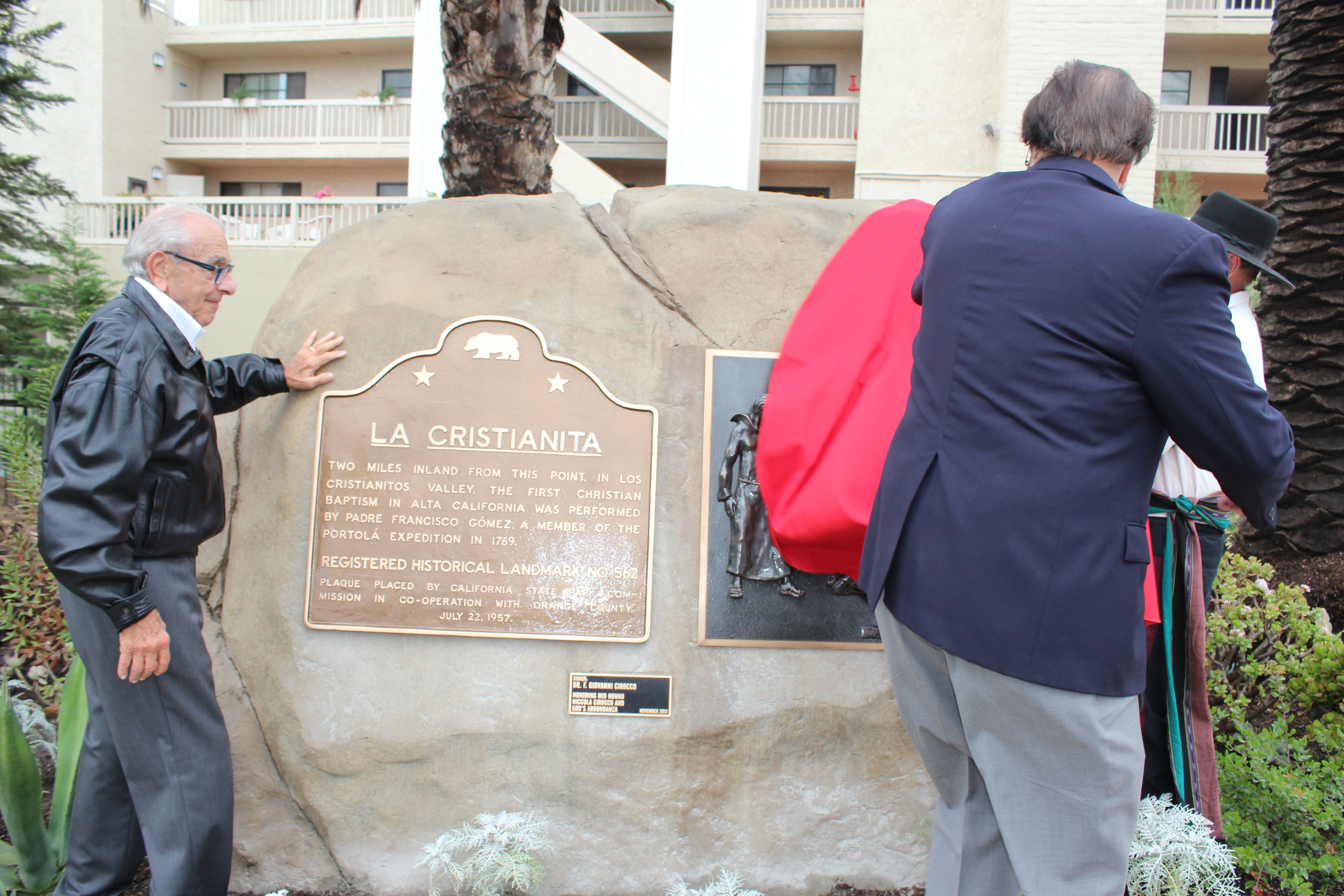 Cirocco unveils the monument with help of founding Casa board member Guy Varriano, left, and Mike Fitzsimmons.