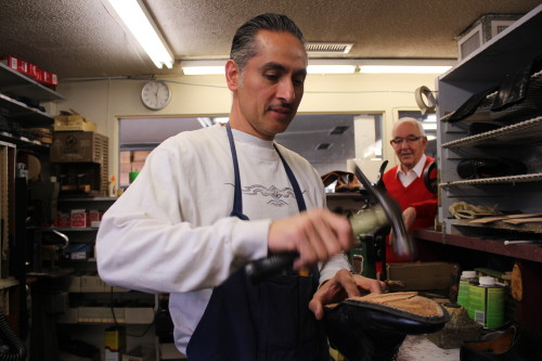Sam Tiberi looks on as Luis Polanco repairs a shoe. Tiberi's business, Sam's Shoes, celebrates its 60th anniversary this weekend. Although starting as a shoe repair shop, Sam's morphed to focus on selling shoes. Photo by Jim Shilander