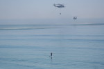 A pair of helicopters take water from the Pacific as a paddleboarder looks on. Photo by Megan Bianco