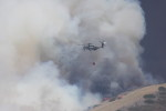 A helicopter makes its way toward the fire with water. Photo by Andrea Swayne