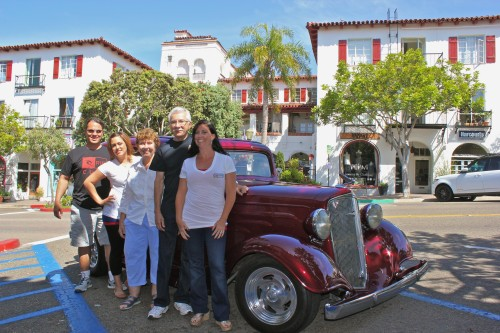 Members of the Downtown Business Association stand in front of a 1935 Chevrolet Sedan belonging to Jim Perez of South Orange County Rods and Customs. The car will be among hundreds on display this Sunday along Avenida Del Mar. Photo: Brian Park