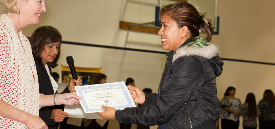 Zeneida Valdez receives a certificate and congratulations from Las Palmas Elementary School Principal Kristen Nelson at the PIQE graduation ceremony Thursday at the Boys & Girls Club of the South Coast Area. Photo: Fringe Photography/Kristen Ruth