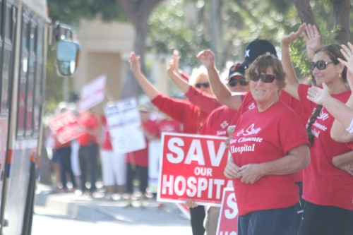 People wave signs on Monday in favor of keeping the San Clemente hospital's emergency rooms open. Photo: Eric Heinz
