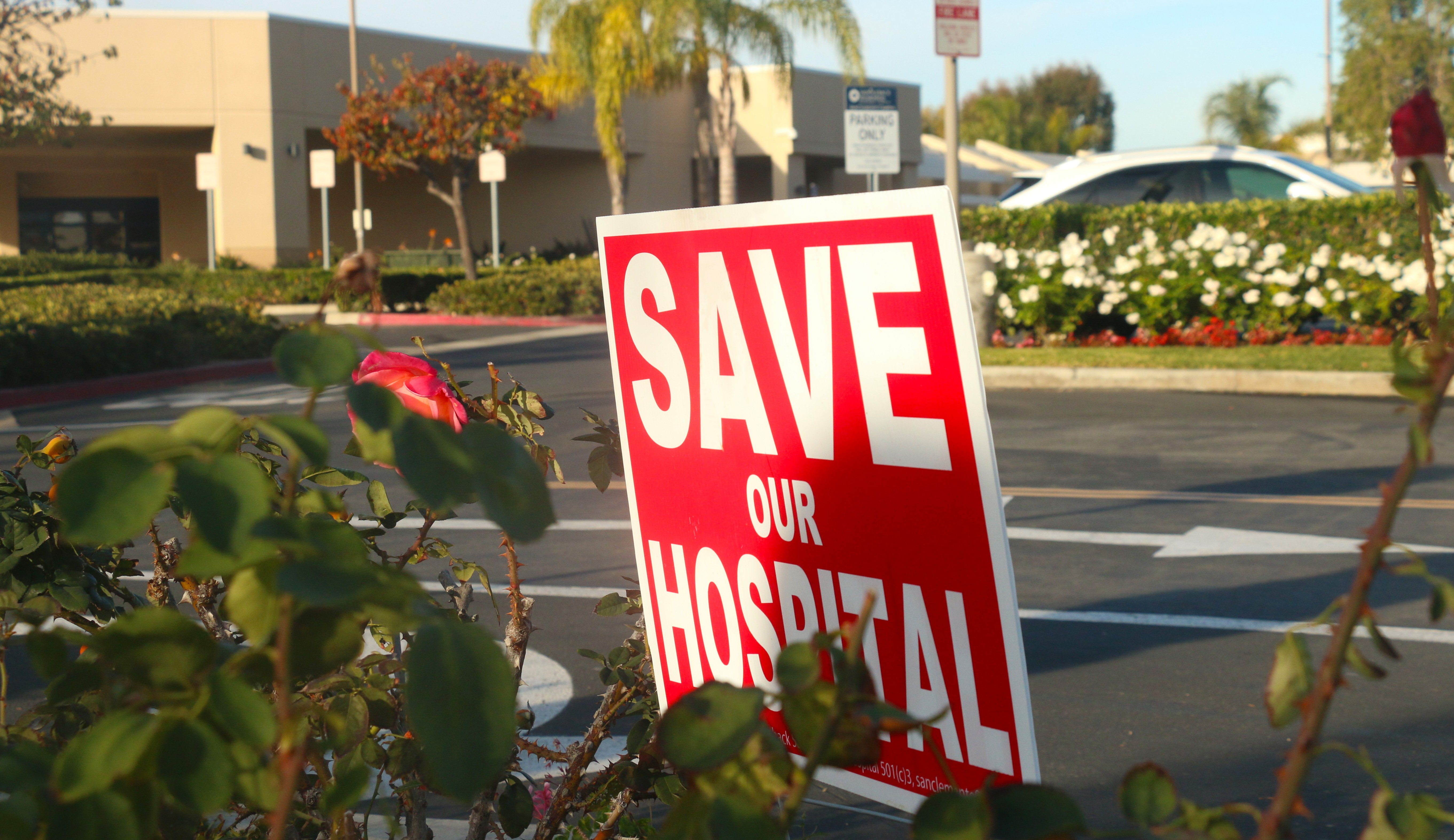 A sign from the community organization Save San Clemente Hospital rests Wednesday in the flower bed adjacent to the Saddleback Memorial Medical Center emergency room. Photo: Eric Heinz