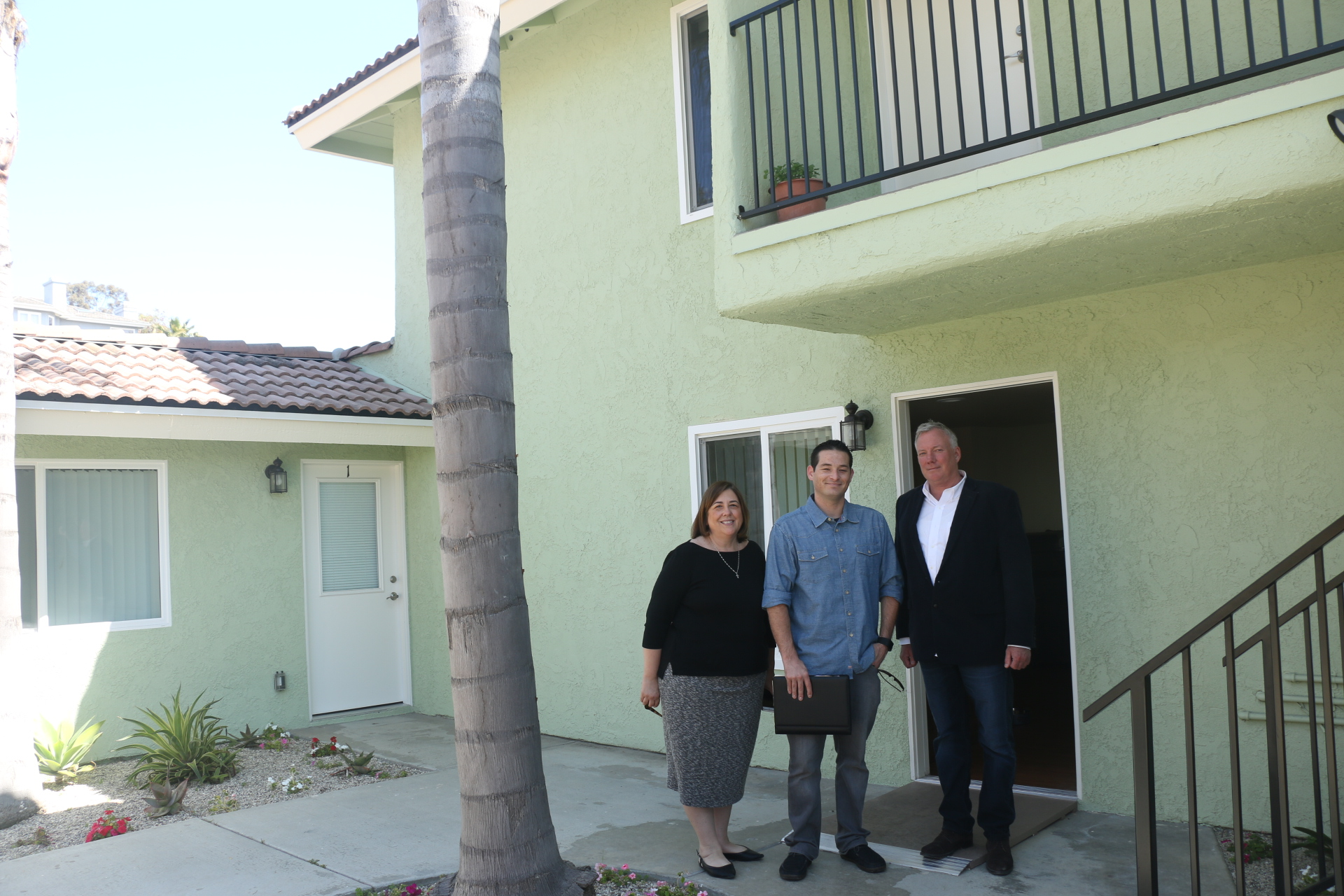 Friendship Shelter representatives (L to R) Dawn Price, David Cox and Mark Miller stand in front of the Henderson House apartments. Photo: Eric Heinz