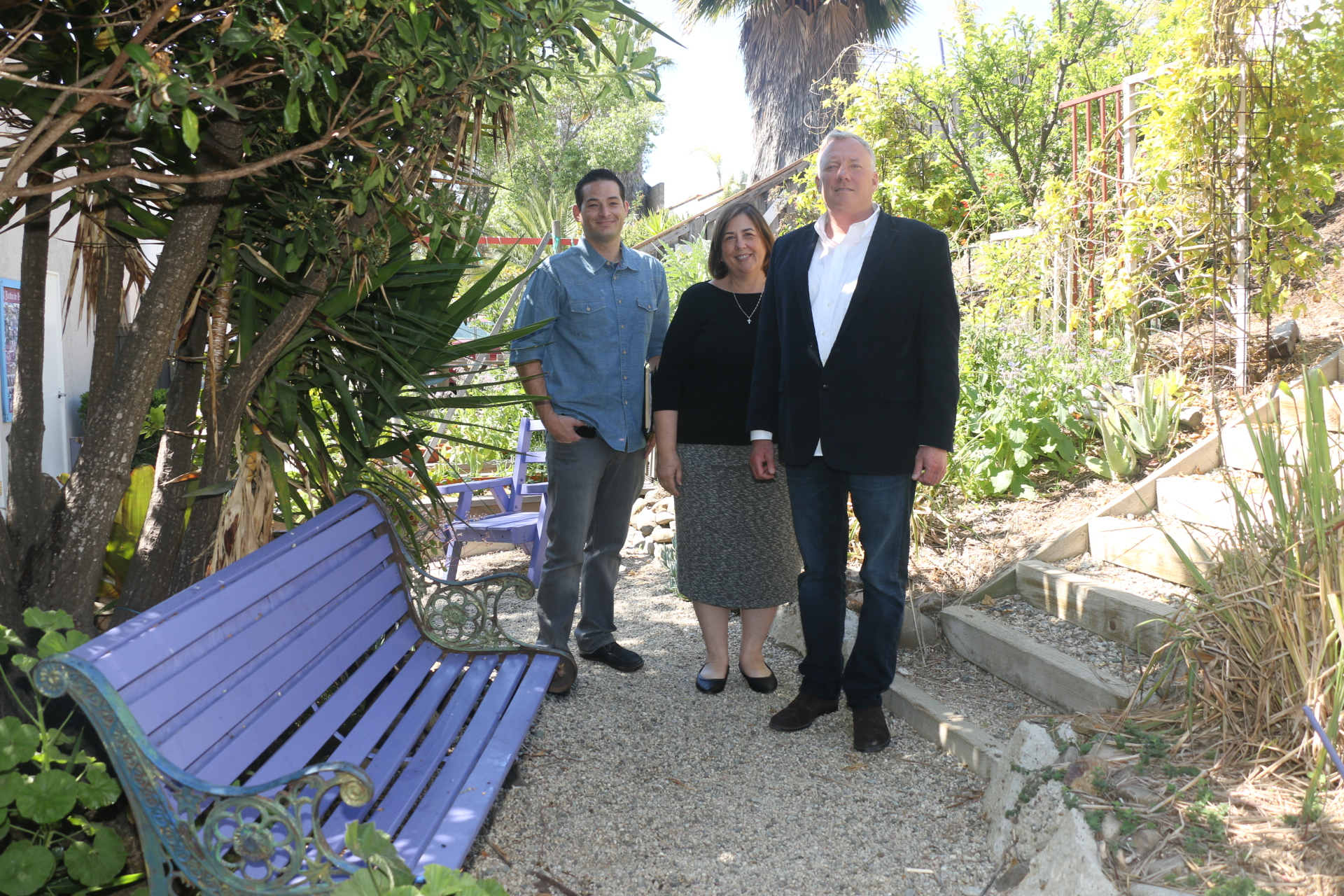 Friendship Shelter representatives (L to R) David Cox, Dawn Price and Mark Miller stand in the garden maintained by the Henderson House apartment residents. The program recently reopened after a complete renovation. Photo: Eric Heinz