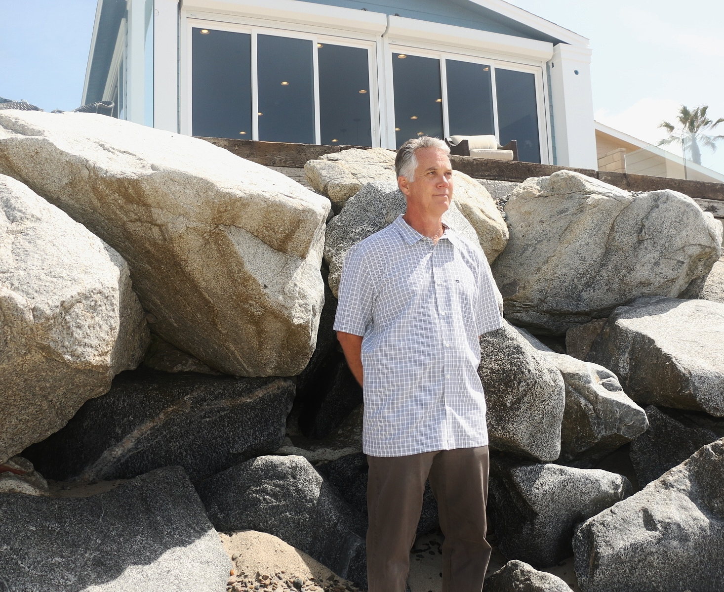 Eric Wills stands in front of the sea wall that protects his Capistrano Shores home on Friday, April 15. The Pacific Legal Foundation filed a lawsuit on Wills behalf on Friday challenging the California Coastal Commission's requirement he waive his rights to maintain a sea wall after he put in a new home in 2014. Photo: Eric Heinz