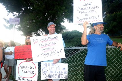 People hold signs in protest on Wednesday, Aug. 17, of a potential sober living residence on the 2900 block of Via San Gorgonio in San Clemetne. Photo: Eric Heinz