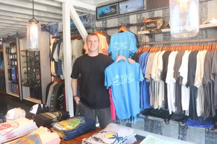 Salt Life store manager Bradley Wilson holds up some of the company's apparel at the retail shop, located at 157 Avenida Del Mar in San Clemente. The store opened Sept. 1. Photo: Eric Heinz