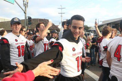 Kalvin Shahnavaz-Khan high-fives fans as the Triton football team walked down Del Mar. Photo: Eric Heinz