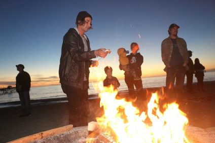 Shon Miller, executive director and founder of San Clemente Beach Conservation Program, makes a s'more during the fire pit gathering following a day of beach cleanup on Friday, Jan. 6. Photo: Eric Heinz