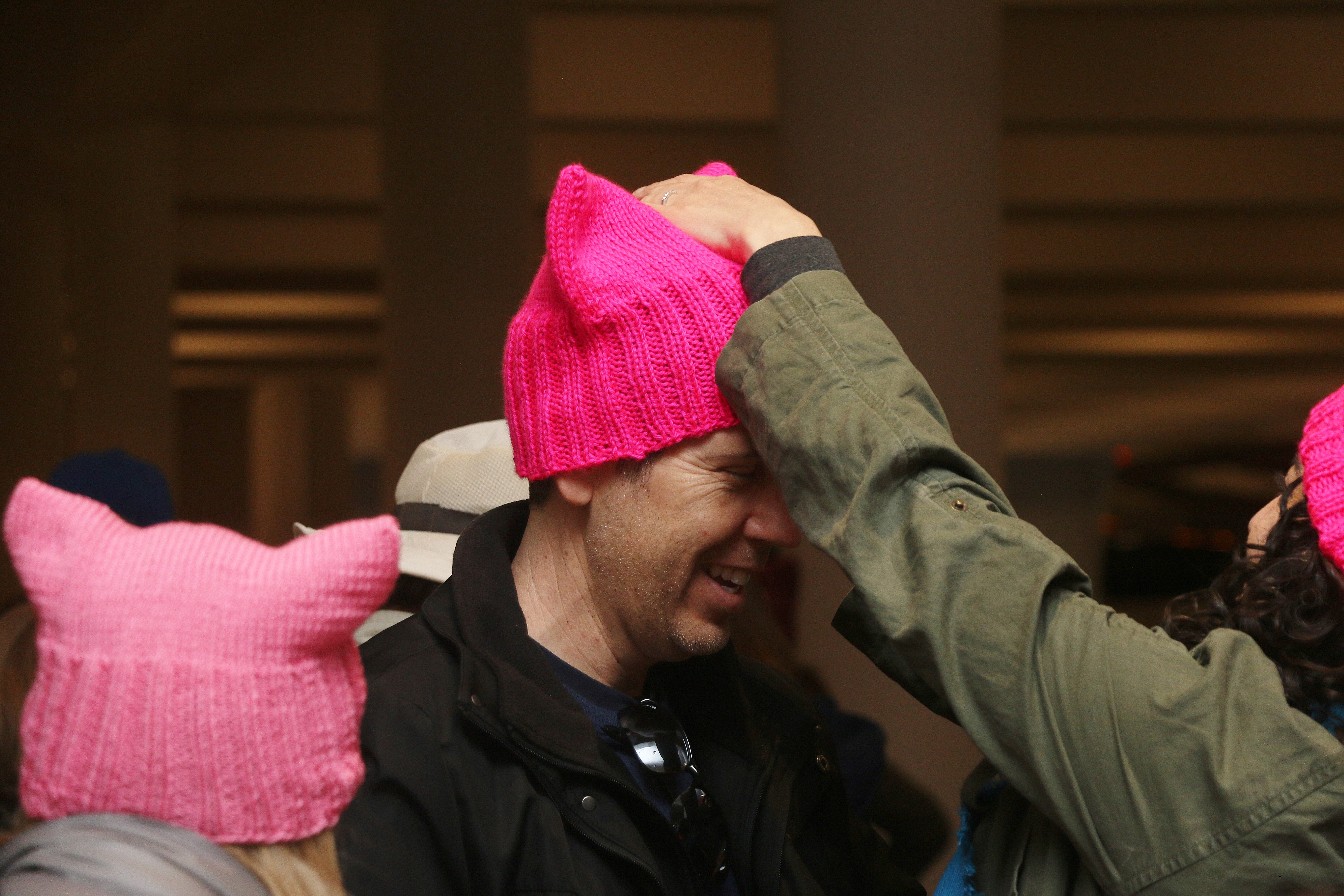 "David Gollom waits for the buses to Santa Ana while his wife, Stephanie Rothschild, places a pink hat on his head. The hats were made as a symbol of marchers' unity in Saturday's Women's March on Washington ""sister march."" Photo: Eric Heinz"
