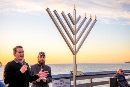 Mayor Pro Tem Tim Brown and Rabbi Mendel Slavin speak to a group of gatherers on Dec. 26 at San Clemente Pier. Photo: Matt Larmand