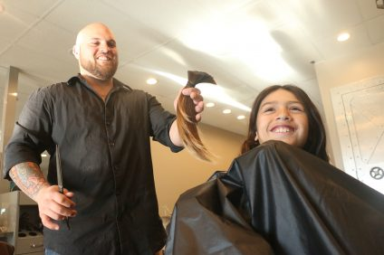 Logan Gallegos, left, a hair stylist at Curtis Michaels hair salon in San Juan Capistrano, holds the locks of Luke Acuna, 9, of San Clemente, on Friday, Jan. 6. Acuna decided to donate his hair to Wigs for Kids charity. Photo: Eric Heinz