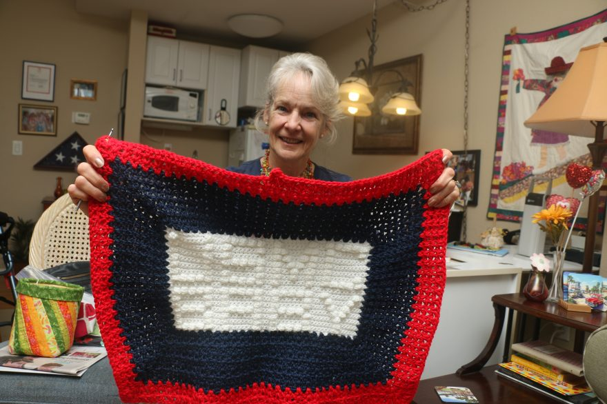 Annette Leinen, a member of the San Clemente Knit Wits, shows her USMC baby blanket she made for infants at Camp Pendleton. Photo: Eric Heinz