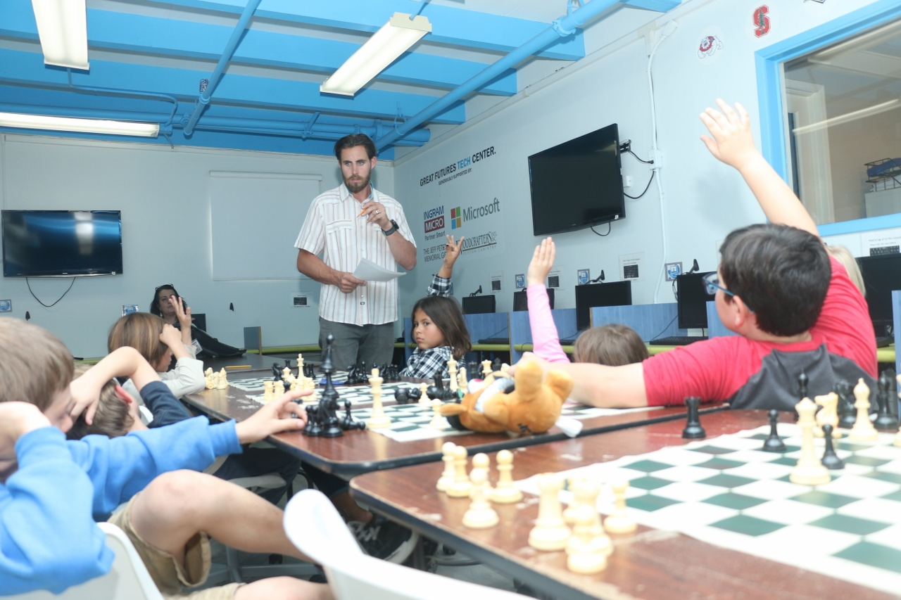 Joshua Host, standing, had been coaching students of the chess club at the Boys & Girls Club of the South Coast Area.