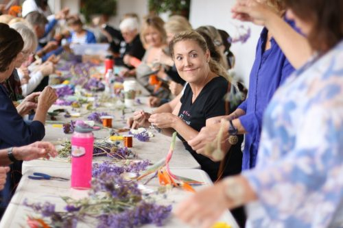Volunteers help put together strands of flowers and assorted items for an exhibit conducted by Rebecca Louise Law, a British artist who does colorful installations. Photo: Eric Heinz