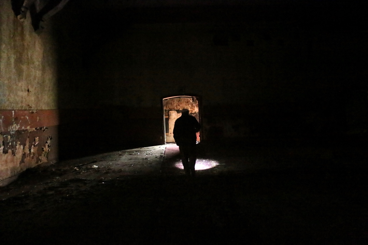 Daniel Conrardy walks through the darkness of the Miramar Theater on June 8, guiding his way by flashlight. Photo: Eric Heinz