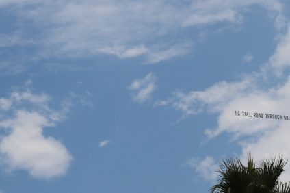 """A plane flies with the message """"No Toll Road Through South Orange County"""" on Saturday, July 15, above the events at the San Clemente Ocean Festival. Photo: Eric Heinz"""