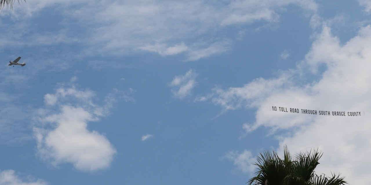 "A plane flies with the message ""No Toll Road Through South Orange County"" on Saturday, July 15, above the events at the San Clemente Ocean Festival. Photo: Eric Heinz"