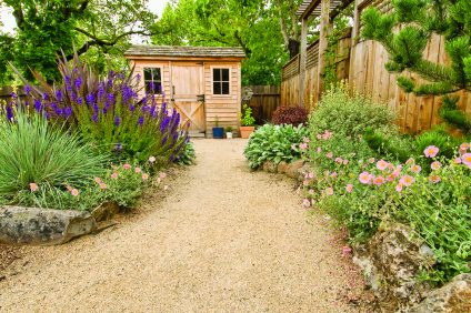 beautifully landscaped backyard with small wooden shed, fence and pathway