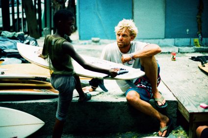 Tanner Gudauskas discusses surfboards with a grom in 2016 during a Positive Vibe Warriors Foundation mission with young surfers of Jamaica. Photo: Grant Ellis