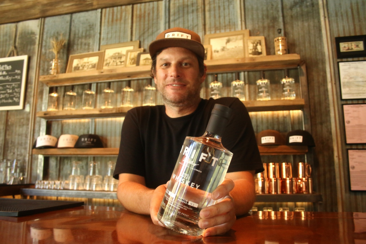 Ryan Winter, founder and owner of Drift Distillery in San Clemente, holds a bottle of his business's vodka. Photo: Eric Heinz