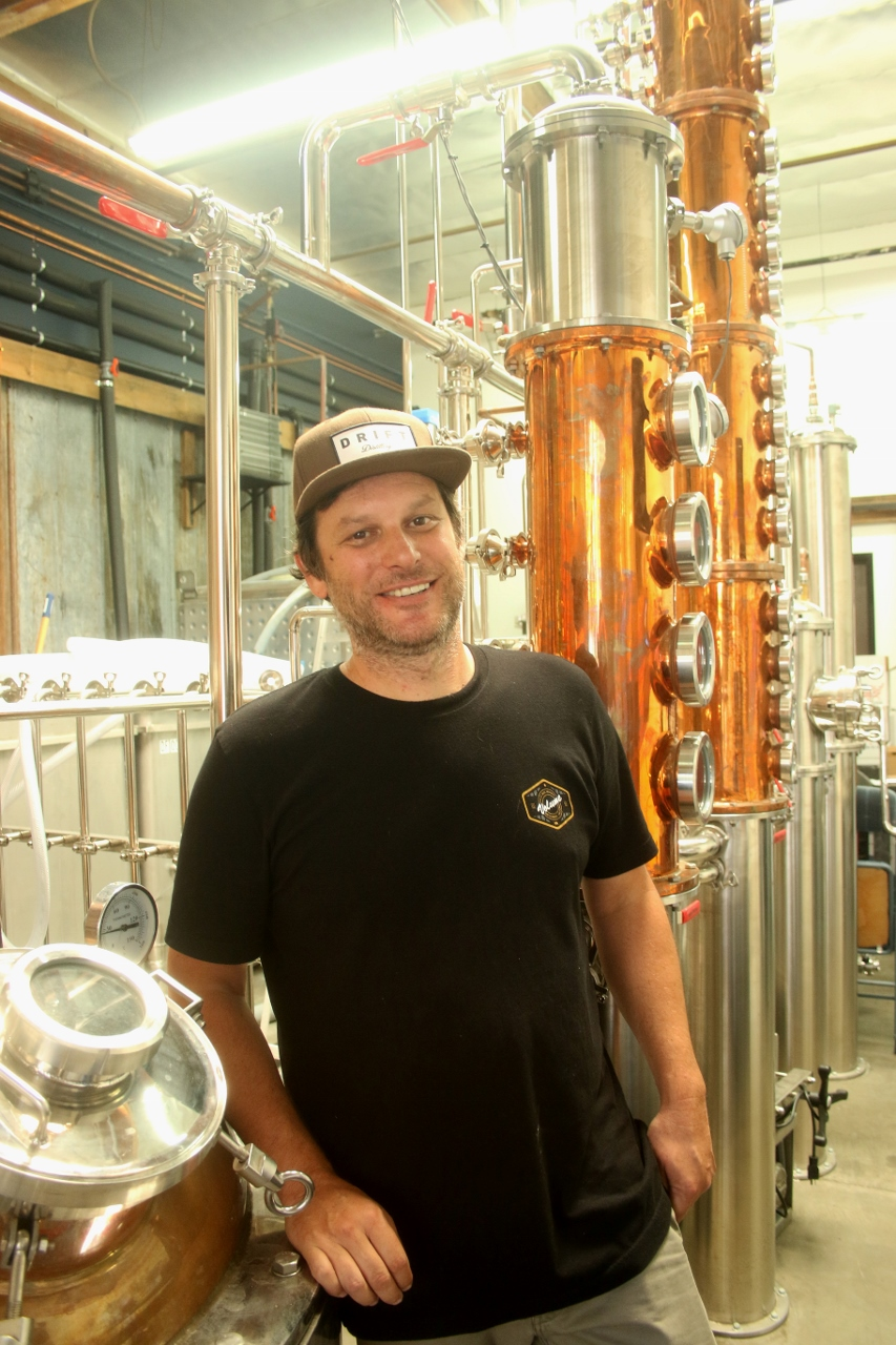 Ryan Winter, founder and owner of Drift Distillery in San Clemente, stands next to the distillery equipment at the business. Photo: Eric Heinz