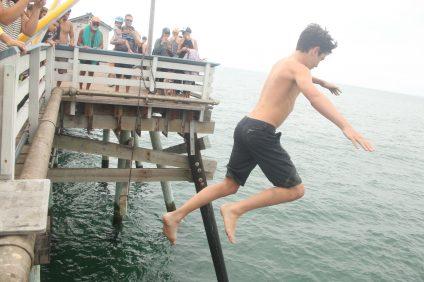 A junior lifeguard jumps off the San Clemente Pier. Photo: Eric Heinz