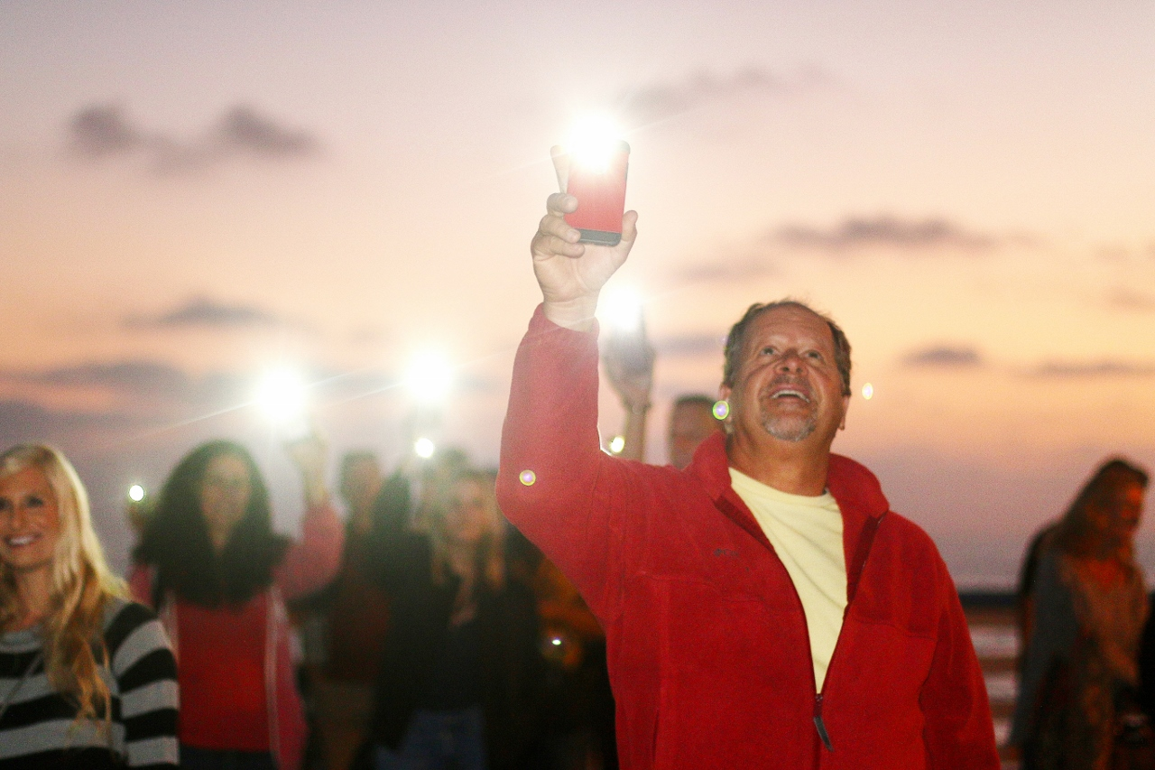 As the sun set, people lit their cell phones and flashlights to participate in Pier Pride's annual fundraising event on Oct. 13.