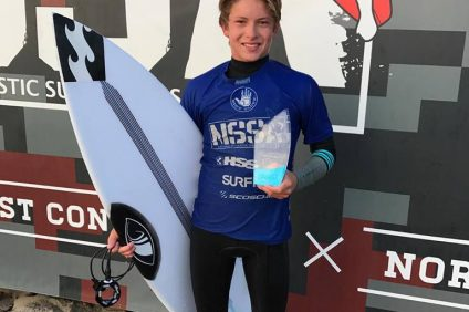 Liam Murray, on the sand in Newport with first-place hardware in hand. Photo: Courtesy of NSSA