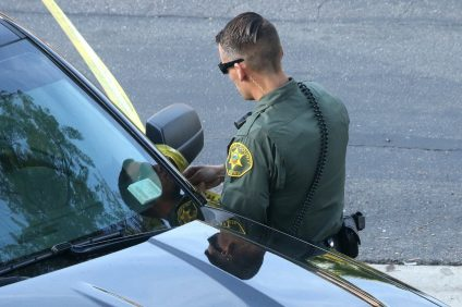 An Orange County Sheriff's Department deputy puts police line tape around a portion of  the Vista Pacifica residential complex on Monday, Dec. 18. Photo: Eric Heinz