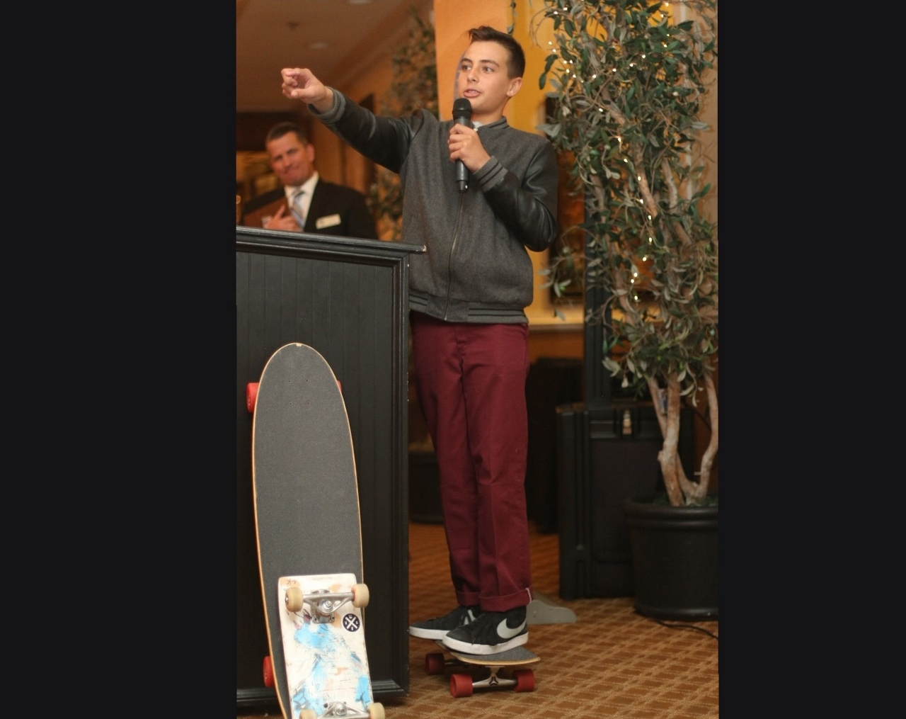 Carson Kropfl speaks to the audience while standing on a Locker Board, which he invented.