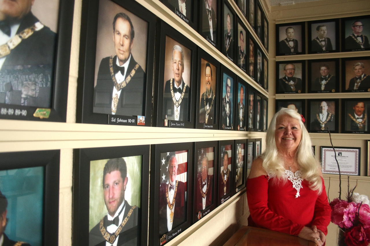 Susan Phillips is to be appointed the first female president of the San Clemente Elks Lodge on Saturday, March 17. Pictured, she poses next to photos of past presidents of the San Clemente branch. Photo: Eric Heinz
