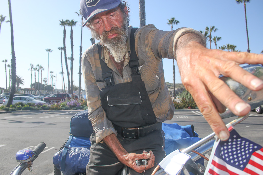 A homeless man who goes by the name Nick adjusts an American flag on his bicycle, his main mode of transportation and place for storage, near the Ole Hanson Beach Club on April 9.  Photo: Eric Heinz