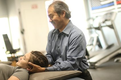 Daniel Souza, owner and president of SCOR Physical Therapy, Inc., demonstrates his work on an employee. The business has been in San Clemente for 30 years.  Photo: Eric Heinz