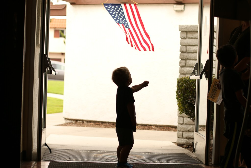 Kati Kalama, 2, views an American flag waving outside the polling station on June 5 at the San Clemente Community Center as his parents wait in line to vote. Photo: Eric Heinz