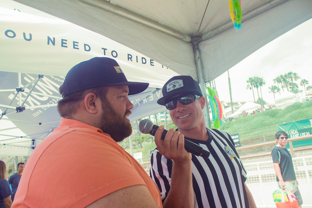 Picket Fence Media sports and outdoors editor Zach Cavanagh, left, takes an impromptu interview on Saturday, July 21, at the San Clemente Ocean Festival. Photo: Eric Heinz