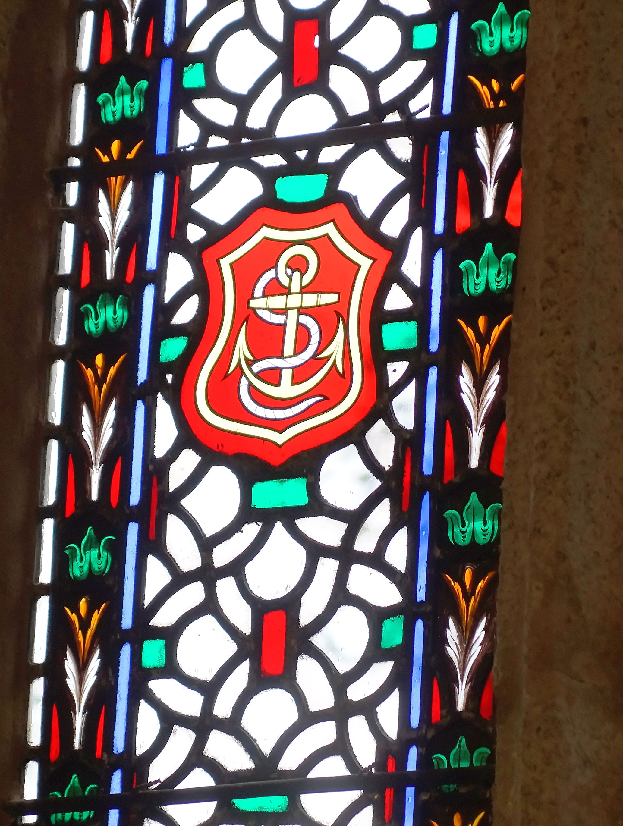 A stained-glass window in the English church at St. Clement, Cornwall, shows an anchor with a cross. The looping rope appears to form the letters SC. Photo: Fred Swegles