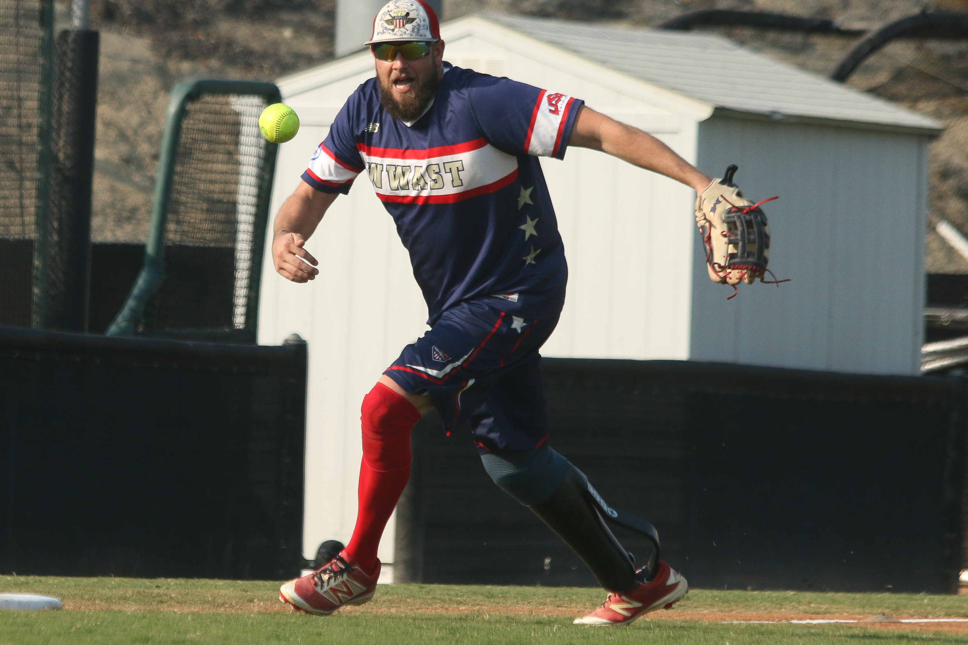 Cody Rice, of the Wounded Warrior Amputee Softball Team, makes a play on a ground ball during a game against the CHP Capistrano team on Saturday, Nov. 10, at Saddleback College. Rice was in the U.S. Army and had part of his right leg removed after stepping on an IED while touring in Afghanistan with the U.S. Army in 2012.