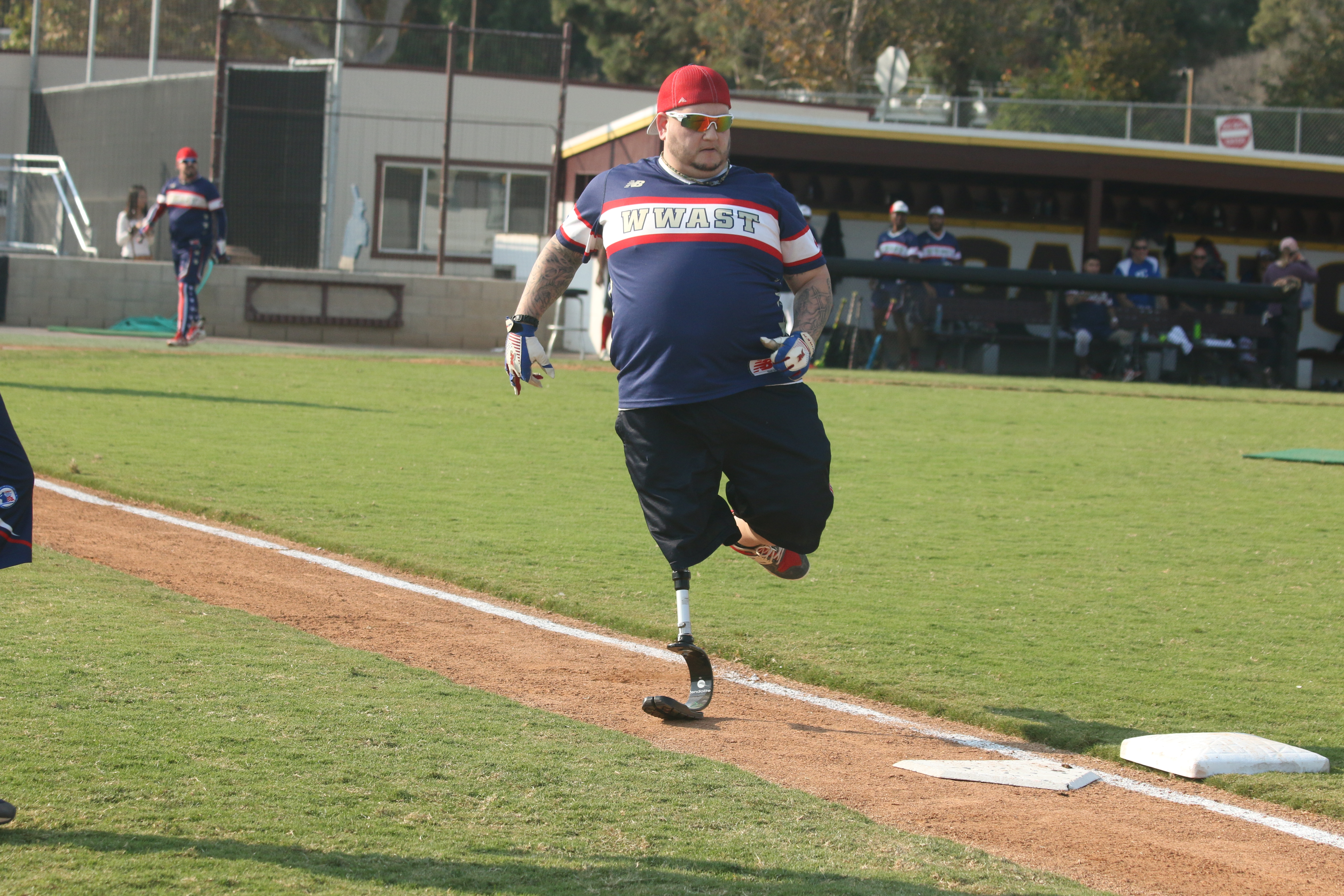 Josh Lopez, a U.S. Army veteran who had his right leg above the knee removed, runs to first base during the Wounded Warrior Amputee Softball Team match on Saturday, Nov. 10, at Saddleback College.