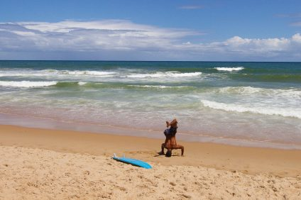 A surfer stretches on a beach in Brazil. Photo: Courtesy of Wikimedia Commons