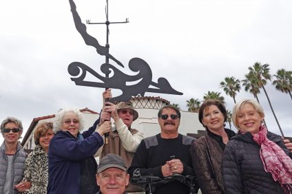 From left, Marilyn Wigglesworth, Mary Ann Comes, Lisa Spinelli, Paul Turney, Mike Fitzsimmons, Larry Culbertson, Laura Ginn and Loretta Busam celebrate a replica weather vane that was about to be hoisted atop San Clemente's Ole Hanson Beach Club on Feb. 20. Photo: Fred Swegles