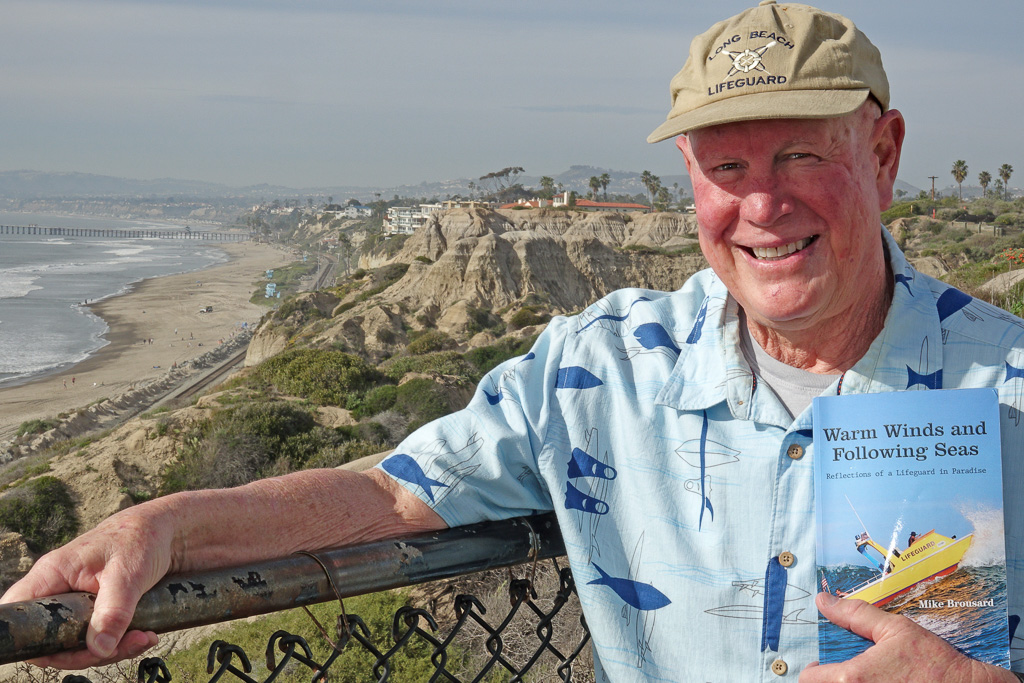 Mike Brousard, whose five-decade career went from rookie lifeguard in 1970 to state lifeguard chief for Doheny, San Clemente and San Onofre State Beaches, displays his book about lifeguarding. His career also included stints protecting lives in Huntington Beach and Long Beach, where he grew up. Photo: Fred Swegles