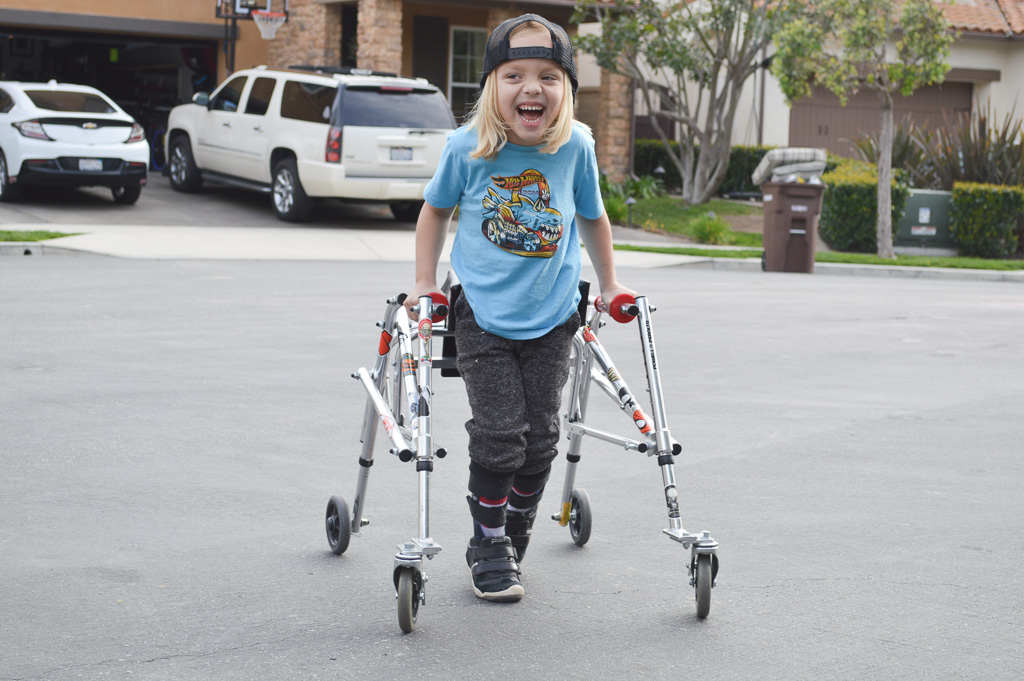 Cru Mercuro, 6, uses a specialized walker to get around. He suffers from a rare form of cerebral palsy, and local residents are gathering to help raise money for his surgery. Photo: Andrea Clemett