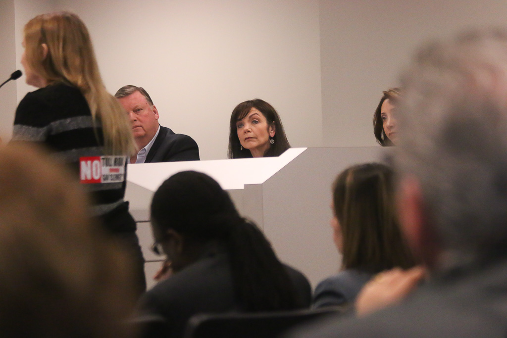 "Councilmember Laura Ferguson, center, listens to a public speaker with a ""No Toll Road"" sticker on her back on Thursday, March 14, at a TCA joint board meeting in Irvine. Photo: Eric Heinz"