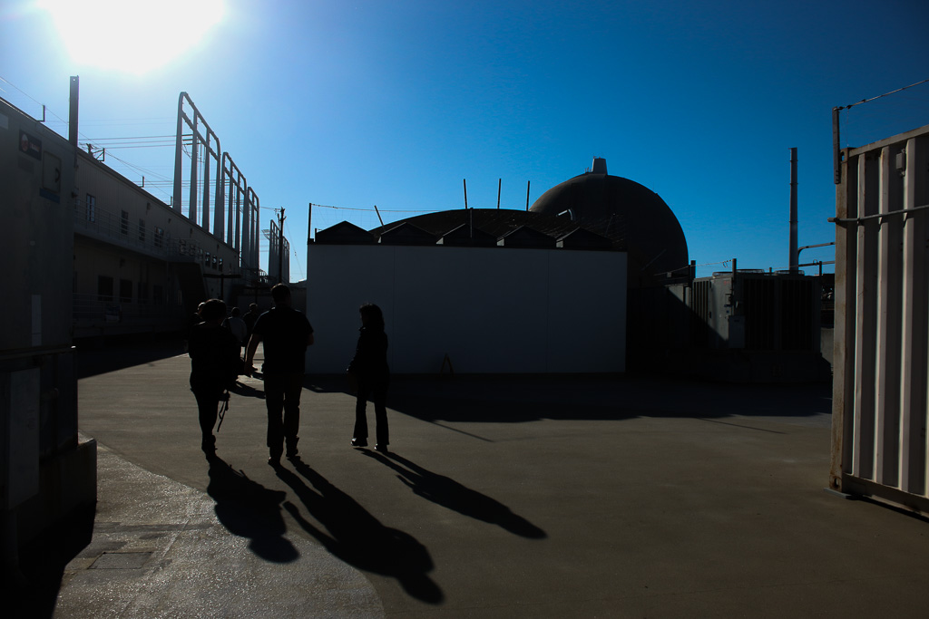 SONGS officials walk past the facilities on-site on March 18. Photo: Eric Heinz