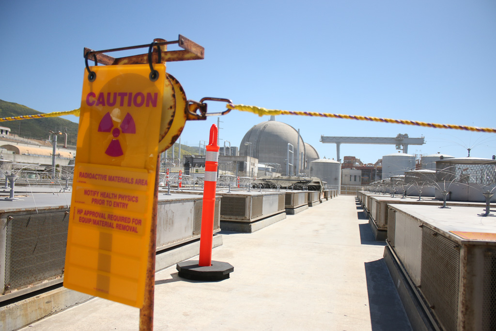 A radiation warning sign hangs between the spent nuclear fuel containment at SONGS on March 18. Photo: Eric Heinz