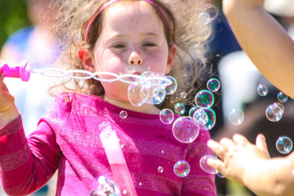 Willow Levine-Wright blows bubbles with other children during the annual Panhe cerebration on Sunday, March 24.